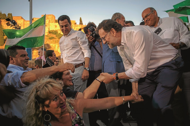 Leader of the People's Party and Spain's caretaker prime minister Mariano Rajoy greets supporters during a campaign meeting in Malaga ahead of the June 26 election. Spain is holding its second elections in six months. Picture: GALLO IMAGES/AFP/JORGE GUERRERO