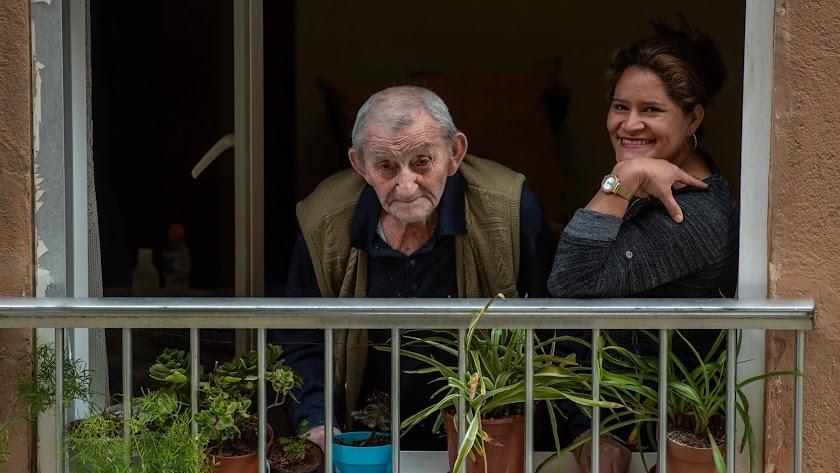 Miguel mira a su enamorada desde su balcón, en compañía de Petrona, su cuidadora.