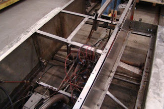 Photo: View of the chassis with the console and fuel tank removed and the new aluminum fire wall in place and ready for attaching to frame.   The original aluminum firewall panel was corroded by battery acid, so the entire panel was removed and used as a template for the new section.