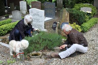 Photo: met de hond aan de paal; onderhoud van het graf