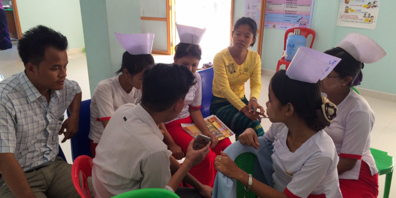 A supervisors sits with a team of community health workers to collect their thoughts on a mobile data collection app