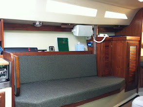 Photo: Port settee, custom galley table folded down, Auto pilot on shelf, new LED light, storage under and behind settee, louvered hanging locker and electronics closet