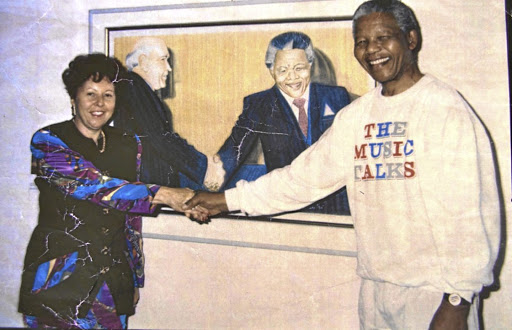 Art heart:  Natalie Knight shakes hands with former president Nelson Mandela at her gallery in Hyde Park Corner in 1990. In the background is a painting of Mandela and former president FW de Klerk by Tommy Motswai, one of many local artists who shared wall space in the gallery with various international artists. Picture: SUPPLIED