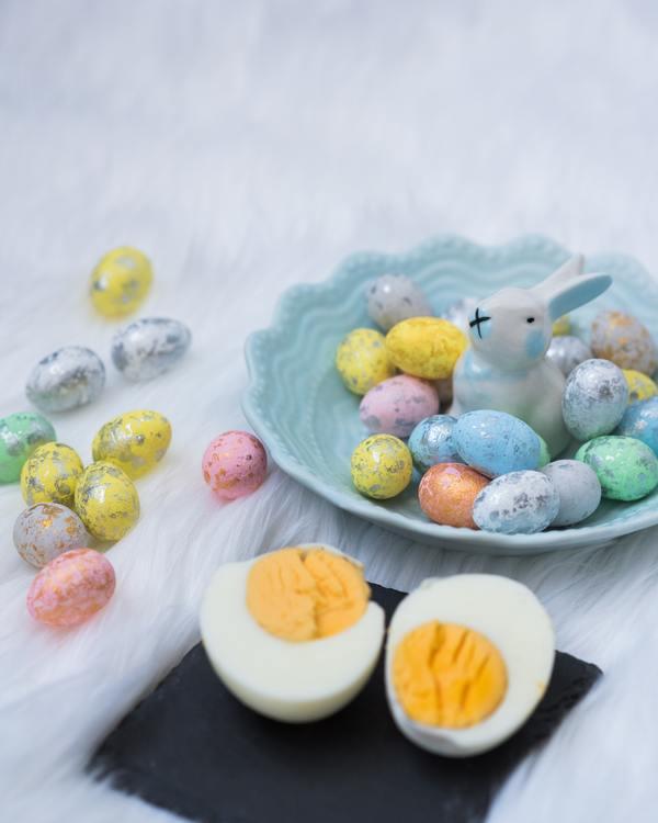 Imagens de um ovo cozido partido ao meio ao lado de um prato de porcelana que tem dentro ovos coloridos e um coelho de porcelana