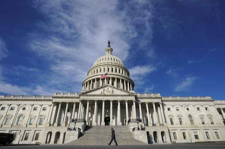 A man makes his way past the US Capitol as the House of Representatives voted on legislation to provide $1.9-trillion in new coronavirus relief, in Washington, the US, February 26 2021. Picture: REUTERS/KEVIN LAMARQUE