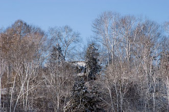 Photo: House in seculded woods on hill covered with snow