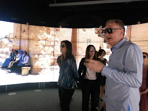 Photo: Paul Bonnington in the foreground, the developer team in the background photo. Paul is wearing special glasses which enable him to navigate the 'world'.  Imagery courtesy of UIC EVL, CALIT2 UCSD, Australian Synchrotron, KAUST, and Monash University