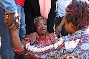 A mother cries after learning her son was stabbed to death outside Forest High School in the south of Johannesburg.
