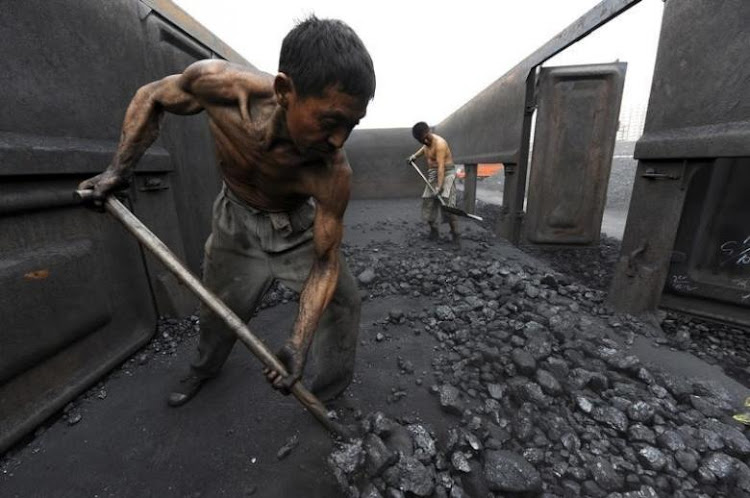 Workers unload coal at a storage site along a railway station in Hefei, Anhui province, China. File picture: REUTERS