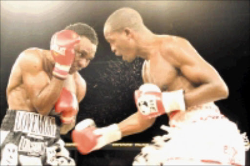 HUFFING: Philip Ndou throws an uppercut at Lovemore Ndou. Lovemore won the 12-round fight on a unanimous points decision to claim the IBO welterweight title at Emperors Palace in Kempton Park. Pic. BAFANA MAHLANGU. 12/07/2009. © Sowetan.