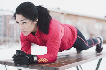 Woman doing plank exercise on bench in city during winter