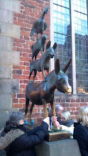 Photo: Bremer Stadtmusikanten - The Bremen Town Musicians - stroking the legs of the donkey is said to bring luck