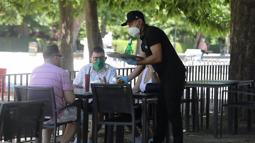 Un camarero atiende a unos clientes.