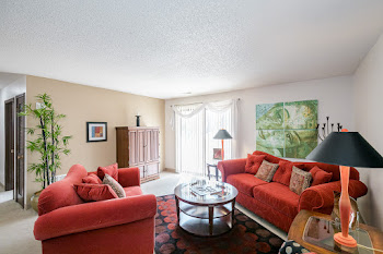 Model living room with light carpet, light walls, and red couches