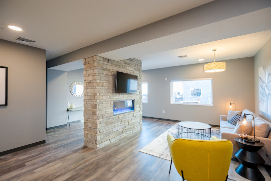 Clubhouse lounge area with seating, a fireplace, and TV