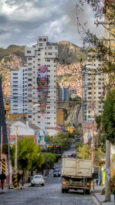 a colorful graffiti watched us as we clicked photos of a steep street in La Paz while backpacking Bolivia