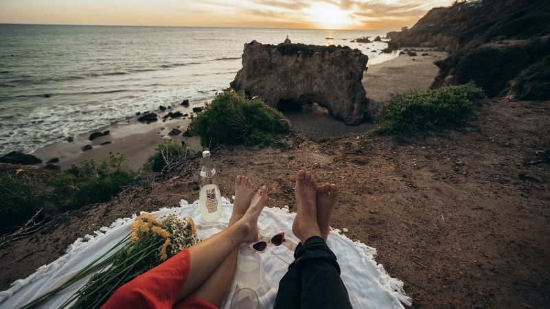 A couple sits on a blanket enjoying the view at El Matador Beach in Malibu, CA.