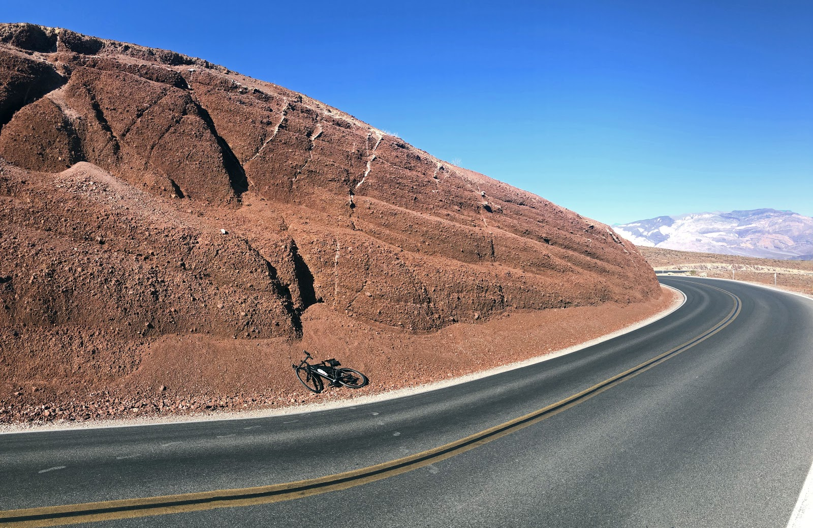 Climbing Panamint Grade by bike - bicycle leaning against red rock
