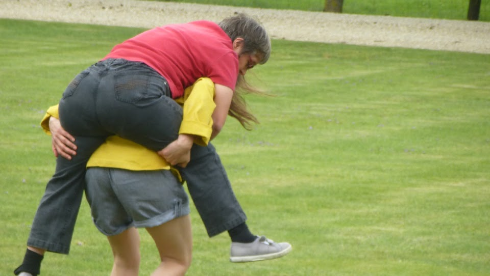 femme portant une personne handicapée sur le dos dans un jardin