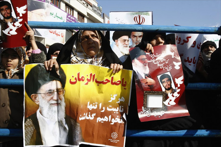 An Iranian woman holds a poster of Iran's Supreme Leader Ayatollah Ali Khamenei in Teheran, Iran. Picture: REUTERS