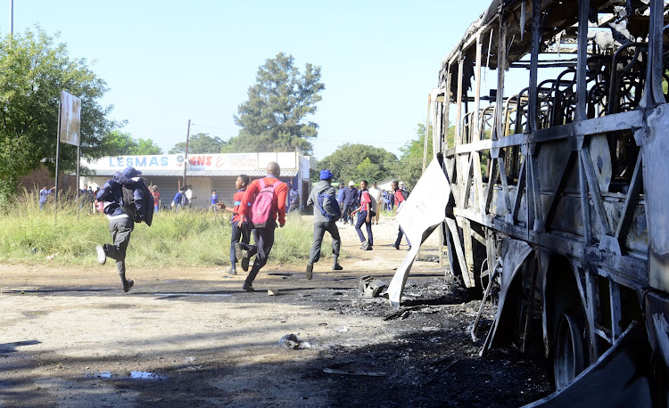 School children run near a burnt bus as residents of Mahikeng protested on the streets of Mahikeng demanding the resignation of Premier Supra Mahumapelo.
