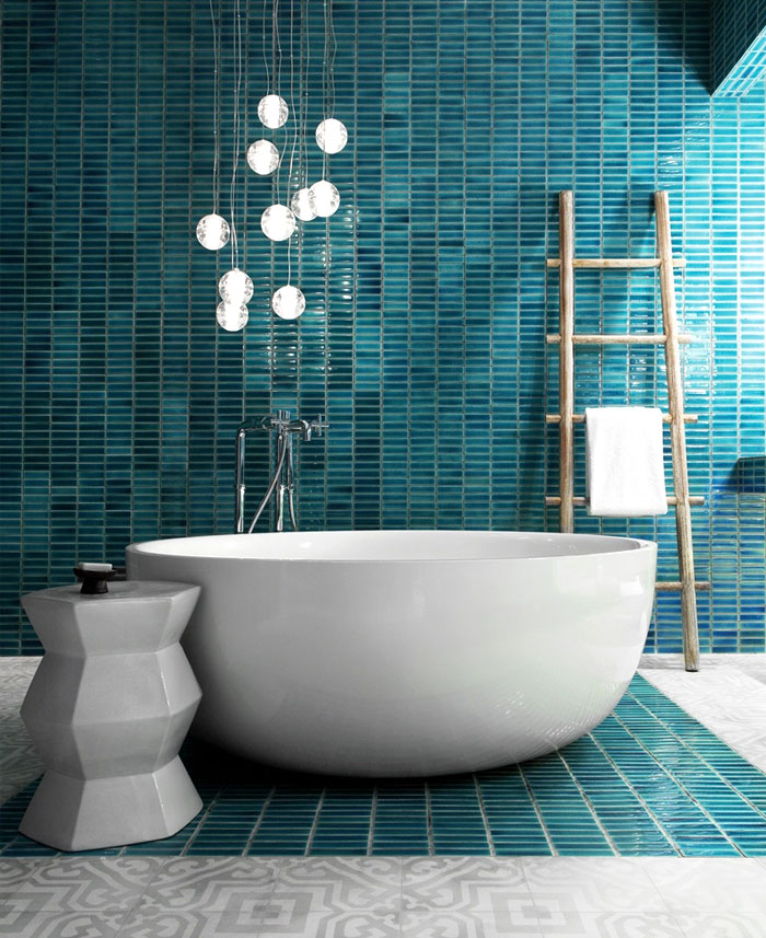 modern bathroom with turquoise blue tile accent wall, wood ladder, white freestanding tub and globe pendant lights