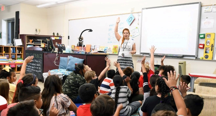 Students raise their hands in class at a school in Phoenix, Arizona