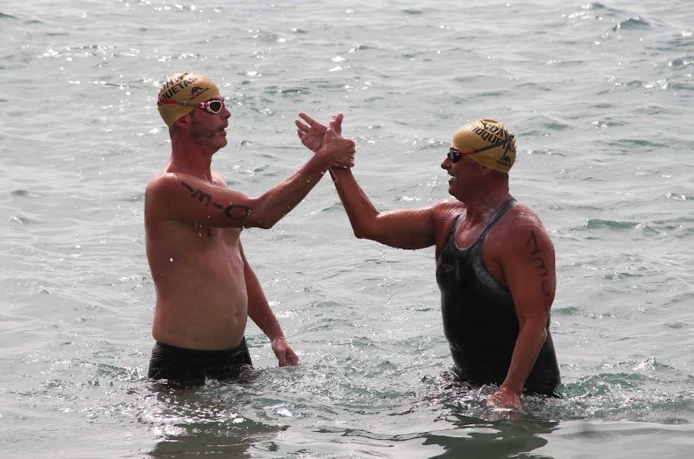 Funcia y PLaza, segundo y tercero de la Golden, chocan la mano al salir del agua.