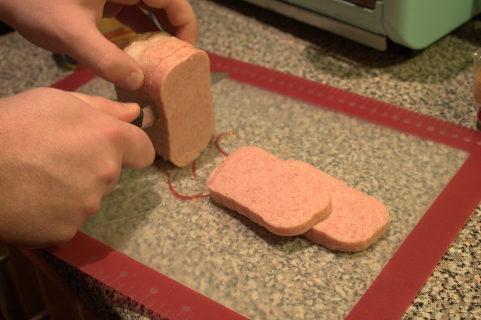 The spam being cut into smaller McRib shaped slabs. Photo by Jessica Collins.