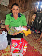 Photo: Volunteer healthcare worker, Kanda, with newborn baby.