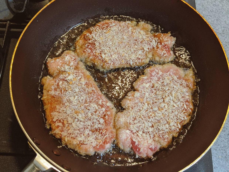 フライパンでラク揚げパン粉を付けたとんかつ用の肉3枚を揚げ焼きしている画像