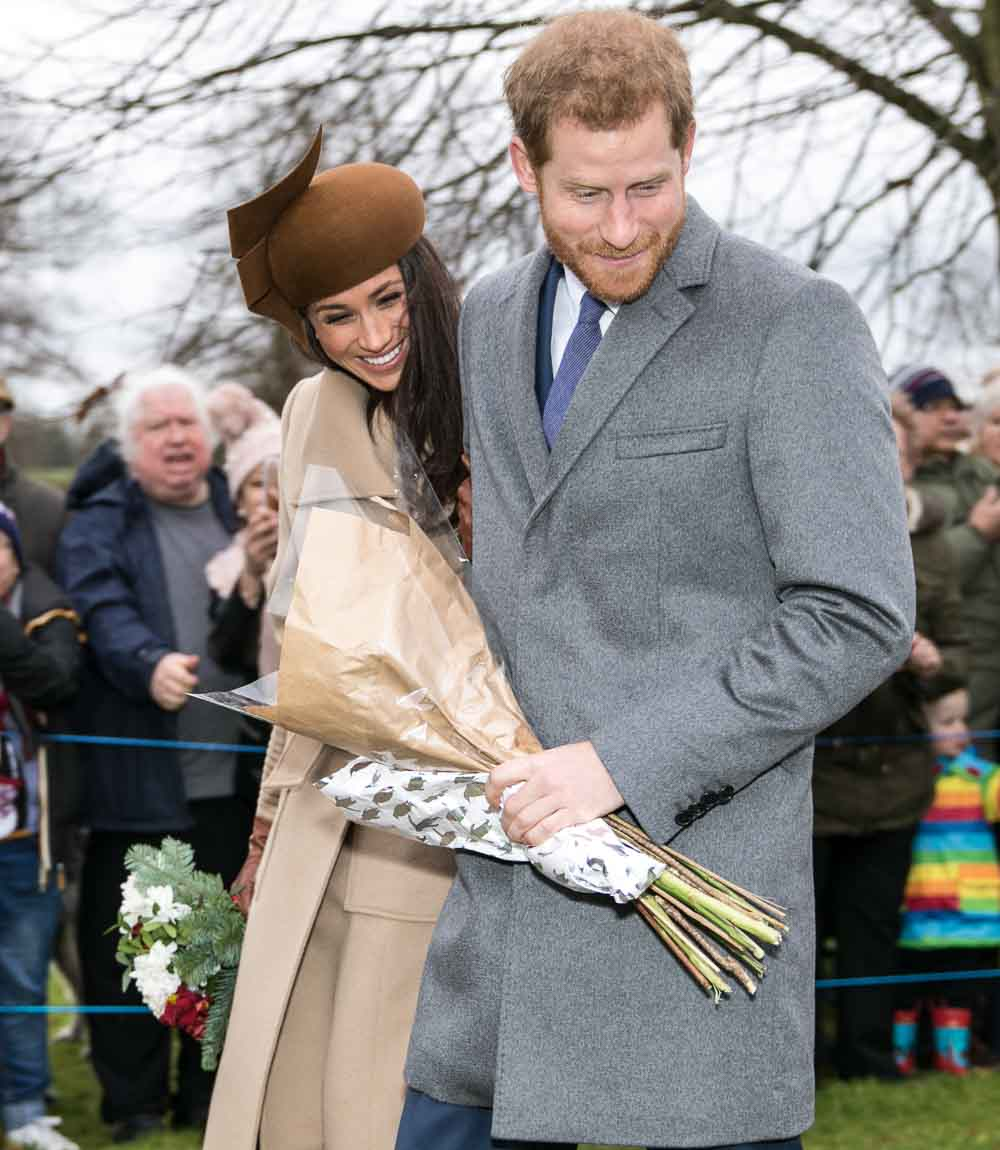 Meghan and Harry embrace, smiling for a crowd, and each hold a bouquet of flowers.