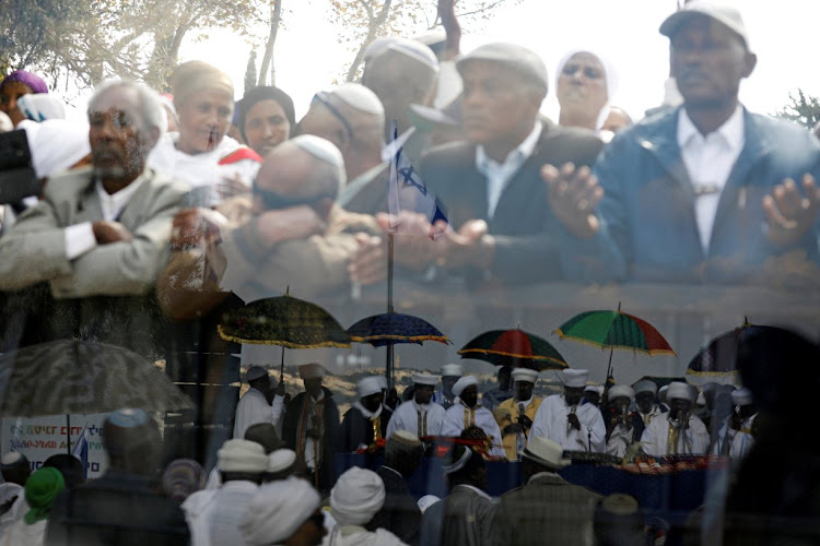Members of the Israeli Ethiopian community are reflected (bottom) in the panel in Jerusalem.