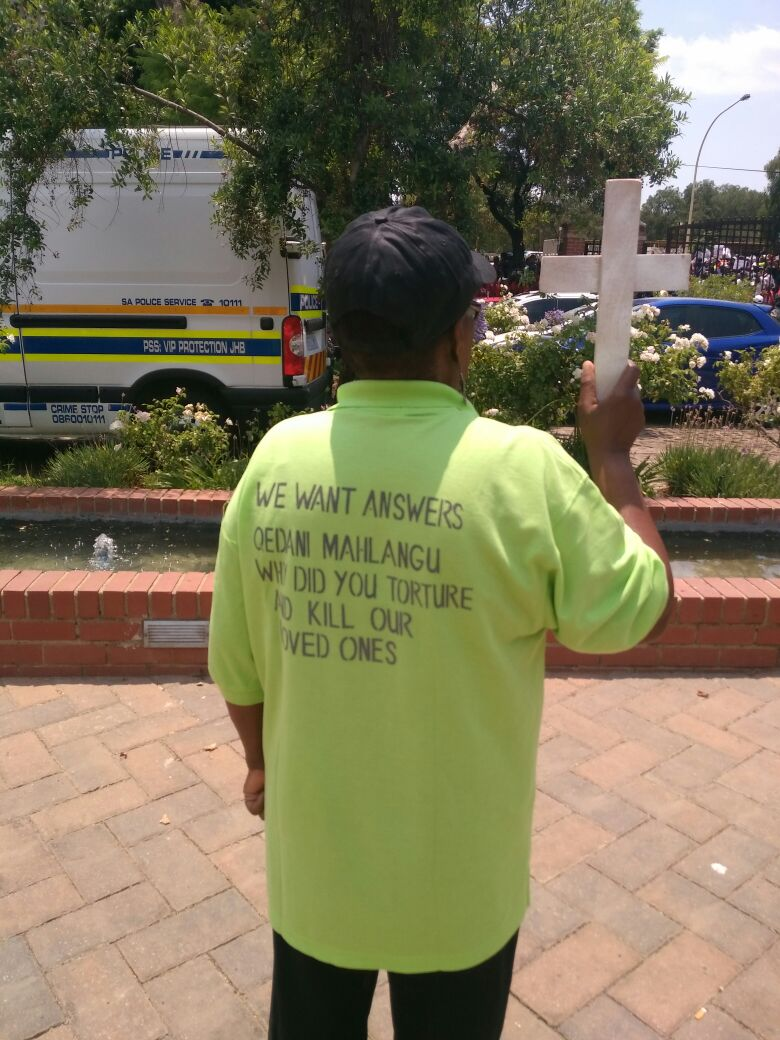 "Family members wore t-shirts with pictures of their deceased loved ones. The back of the t-shirts read: ""We want answers. Qedani Mahlangu' why did you torture and kill our loved ones?"""