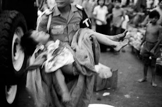 Photo: 21 Apr 1975, Ho Chi Minh City, Vietnam --- A soldier carries a wounded child after the first rocket attacks announcing the North Vietnamese entry into Saigon. Fourteen died and over forty people were injured in the attacks. --- Image by © Jacques Pavlovsky/Sygma/CORBIS