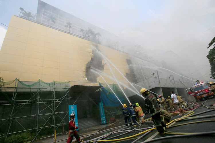 Firefighters douse water after a fire engulfed the Manila Pavilon hotel in Metro Manila, Philippines March 18, 2018.