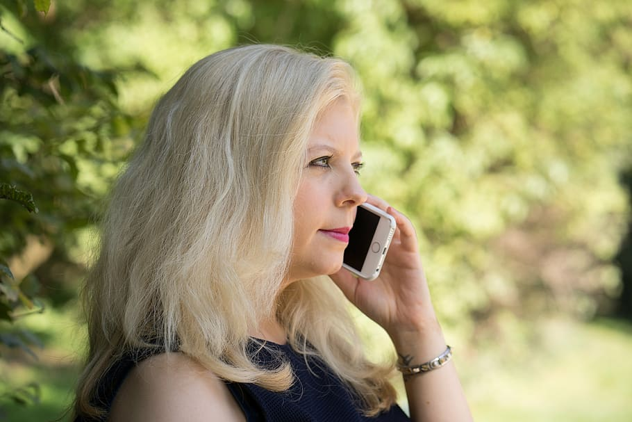 A woman with blonde hair holds a white smartphone up to her left ear with her left hand