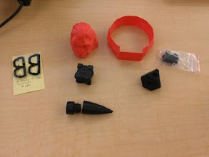 Photo: Pretty much all the objects printed on our M2 so far - the two factory samples, my endstops, the core for one of those cute square gear things, a scaled-down threaded rocket nose cone (thread test, mediocre), and a companion cube.