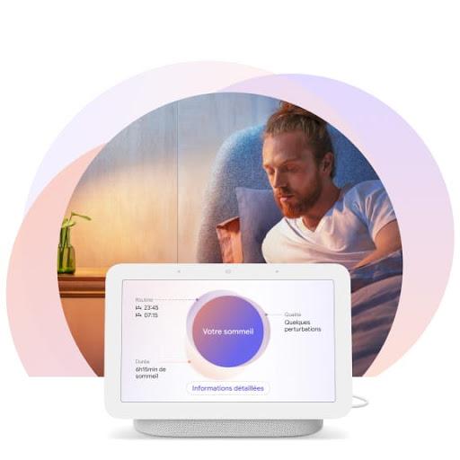 [Image] Un homme est allongé dans son lit et tourné vers l'écran de son NestHub posé sur la table de nuit. L'écran affiche des informations personnalisées sur son sommeil.