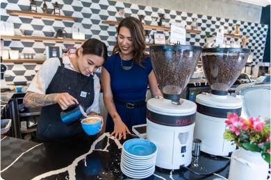 Dos mujeres con cabello castaño lacio llenan una taza azul de café detrás del mostrador de una cafetería.