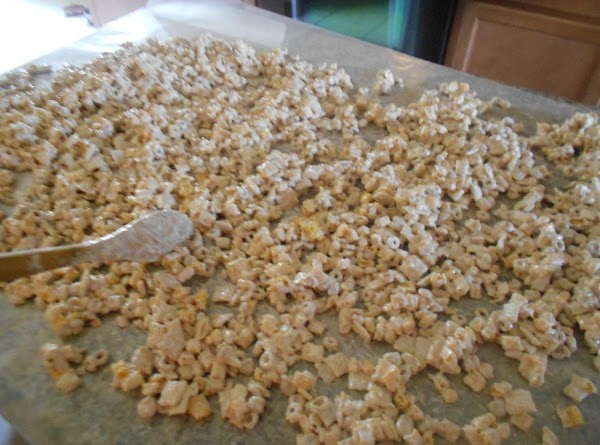 Pour over cereals and nuts in bowl and stir completely.  Pour out onto...