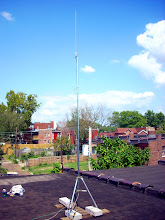Photo: This is a Ubiquiti Bullet2HP access point (attached just 2feet below the dipole, tho not visible), a 12dB omni dipole antenna, and roof tripod anchored with cinderblocks.