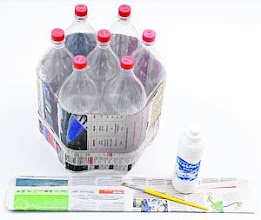Photo: http://artesanatobrasil.net/puff-infantil-de-garrafas-pet-do-professor-sassa/  2 – Encape as garrafas com folhas de jornal. Dê várias voltas e use cola branca para fixar uma parte na outra.