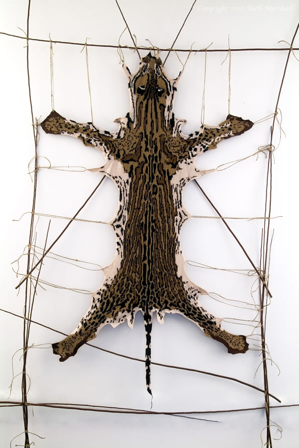 """Photo: #5 Ocelot 2010 53"""" x 32"""" (134cm x 81cm) Hand knitted textile. Interpretation of ocelot based on study of actual pelt at American Museum of Natural History. Male - collected from Peru 1930. Yarn, string, sticks. (C) Ruth Marshall, 2010."""