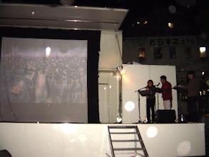 Photo: 2002年10月26日 野外上映会in新開地  今まで星も見えていたのに急に雨が降ってきた、我々、お客さんにも緊張感が・・・このまま途中で終わってしまうのか?