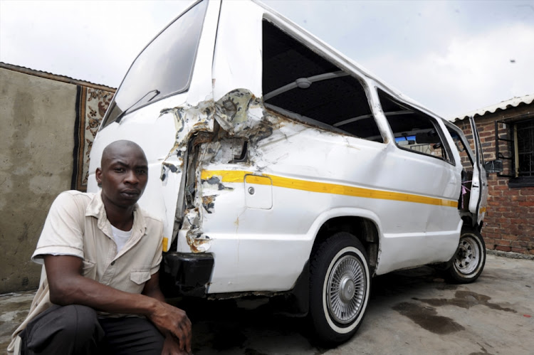 Vusi Dlamini with his damaged taxi on February 10, 2014, in Johannesburg. President Jacob Zuma's son, Duduzane, crashed into Vusi's taxi in Sandton, due to lack of visibility in the rain, on February 9, 2014.