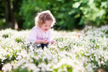 Little girl playing in flower field