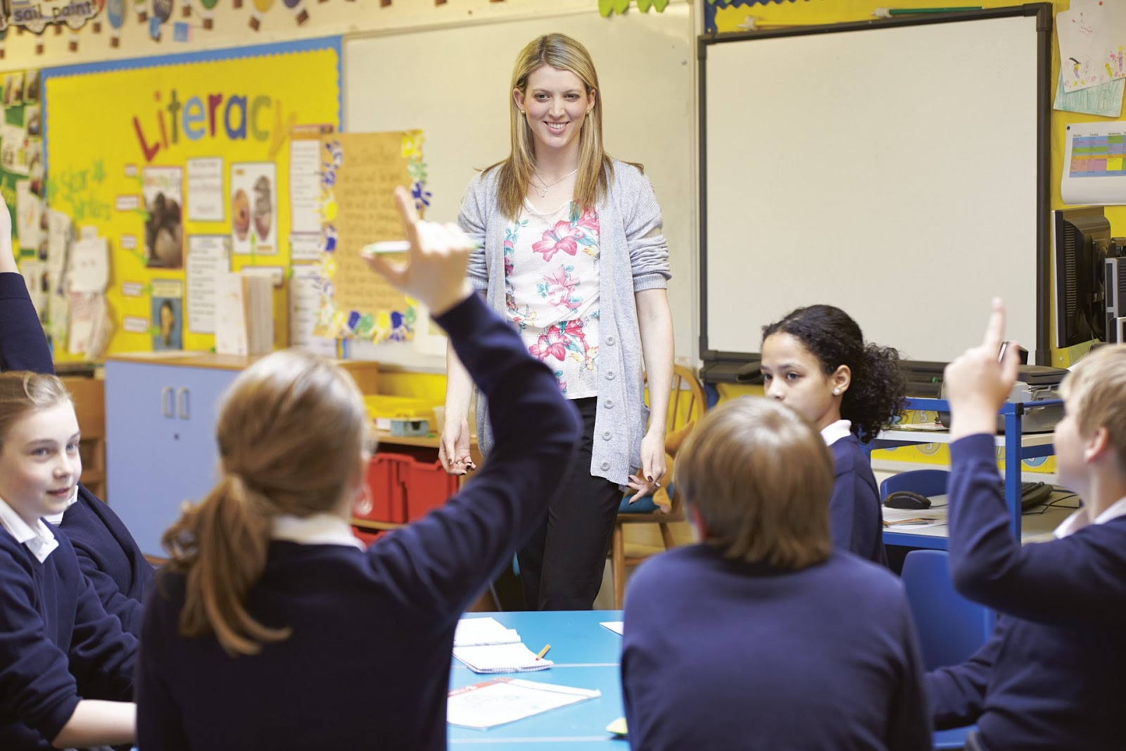 A small group of students engage in a conversation with their teacher. One hand is raised, the teacher and some of the children are smiling. There is a bulletin board in the background with the word literacy on it.