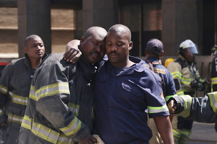Firefighters comfort each other after three of their colleagues died while battling a blaze at one of the government buildings in the Johannesburg city centre.