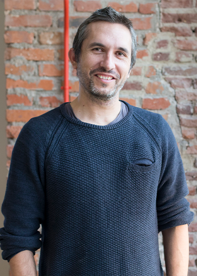Cofounder and CTO, Ferdinand, is smiling at the camera against a brick wall wearing a navy sweater.